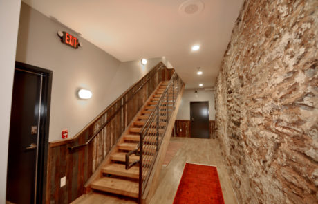 Interior stairwell of loft apartment showing the rustic stone walls